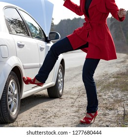 Angry woman kicks car wheel after car accident or some broken spare part