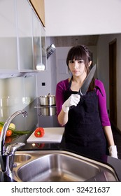Angry woman in kitchen with a knife