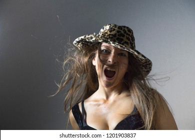 An angry woman with leopard hat and decolletage is looking straight to camera