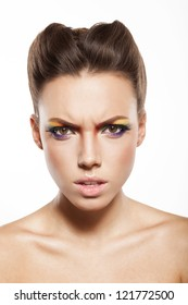 angry woman is looking at camera, beautiful female face with rainbow makeup.