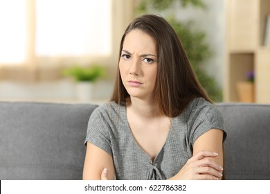 Angry woman looking at you sitting on a sofa in the living room at home