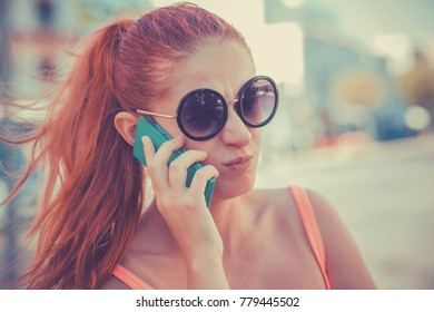 Angry woman phone talking. Closeup young unhappy frustrated disapointed beautiful woman girl lady talking on mobile cellphone on cityscape outdoor background. Negative face expression human emotion