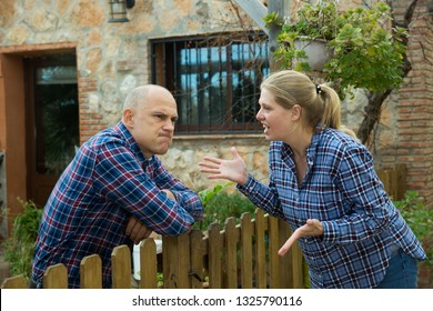 Angry woman quarreling with her male neighbor, talking through wooden fence