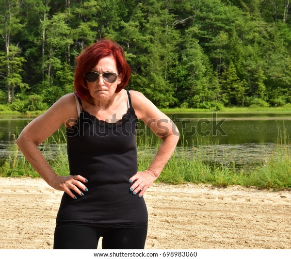 Angry woman with red hair by lake