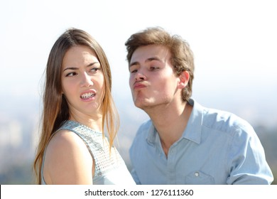 Angry woman rejecting a friend kiss in a sunny day