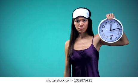 Angry woman showing clock, unable to sleep late at night, insomnia problem