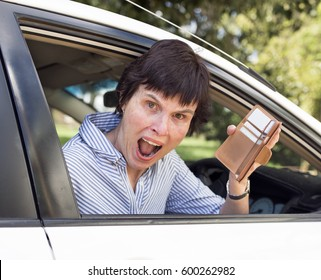 An angry woman sitting in her car screams out as she holds up her wallet missing money.