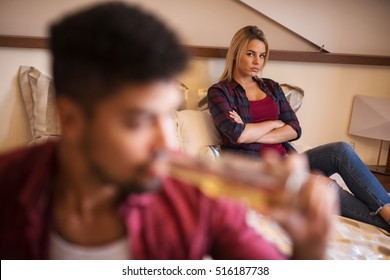Angry woman sitting on bed behind her drunk boyfriend.