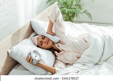 angry woman in sleeping mask holding alarm clock at morning