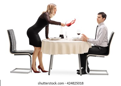Angry woman spilling her drink on a man and yelling at him on a restaurant table isolated on white background
