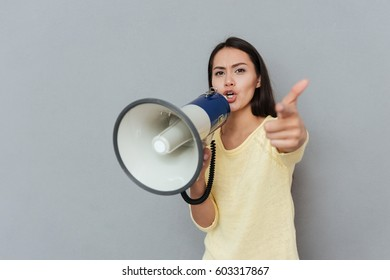 Angry Woman in sweater which screaming in megaphone and pointing at camera over gray background