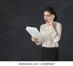 Angry woman talking on mobile at black background. Unhappy girl having unpleasant converasation on smartphone. Modern lifestyle communication and misunderstanding concept, copy space