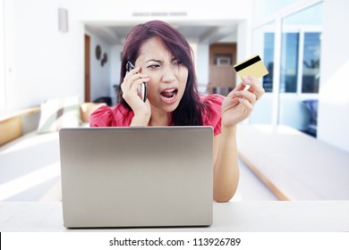 Angry woman talking on the phone with laptop and holding credit card, shot at home