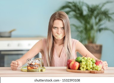 Angry woman with taped mouth, healthy and unhealthy food in kitchen. Diet concept