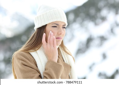 Angry woman using a sking protection moisturizer cream in winter in a snowy mountain