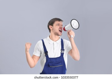 Angry worker shouting into megaphone on grey background