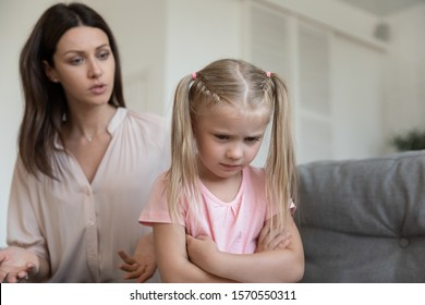 Angry young adult mom scold stubborn fussy upset little kid daughter sulking sit on sofa ignore parent, single mother shout at unhappy preschool difficult child girl punish for bad behavior at home