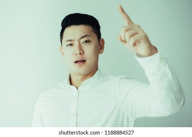 Angry young Asian man wagging finger at camera. Boss scolding employee. Business and management concept
