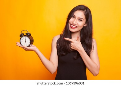 Angry young Asian woman point to a clock on yellow background