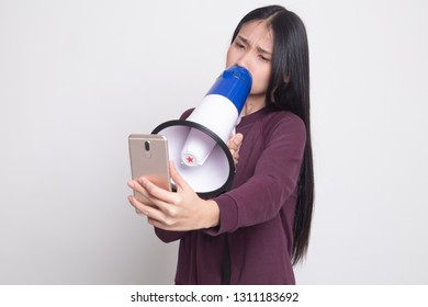 Angry  young Asian woman shout with megaphone to mobile phone on white background