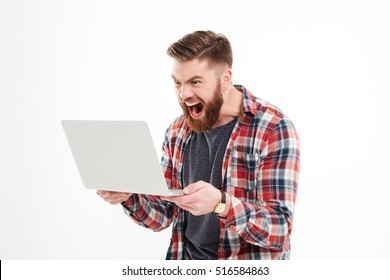 Angry young bearded man in plaid shirt screaming at laptop in hands over white background