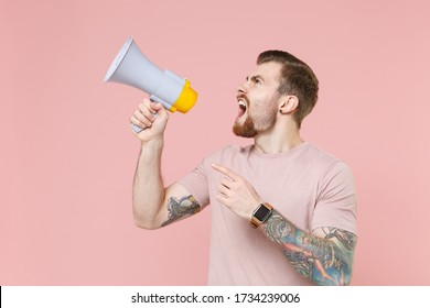 Angry young bearded tattooed man guy in pastel casual t-shirt posing isolated on pink background studio. People lifestyle concept. Mock up copy space. Scream in megaphone, point index finger aside up
