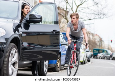 Angry young bicyclist shouting while swerving for avoiding dangerous collision with the open door of a 4x4 car on a busy street in the city