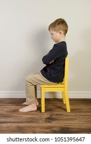 An angry young boy sits on a yellow time out chair