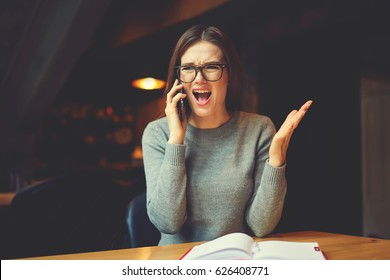Angry young business woman communicating via smartphone while sitting in coworking space discussing problems with organization working process, irritated female executive manager supervising employee
