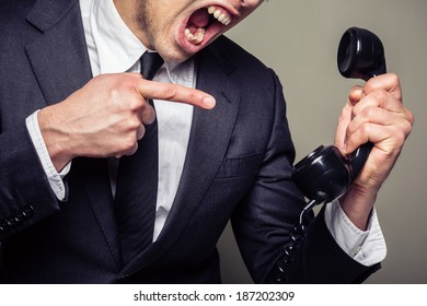An angry young businessman is on the phone and screaming