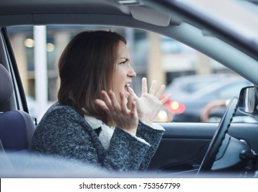 Angry young businesswoman driving her car