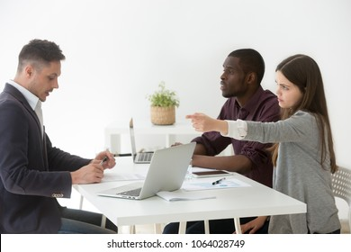Angry young businesswoman firing upset businessman at multiracial team meeting, dissatisfied boss dismissing stressed employee for bad work or misconduct, conflicts and discrimination at work concept