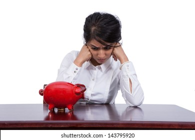 Angry young businesswoman looking at a piggy bank at her desk