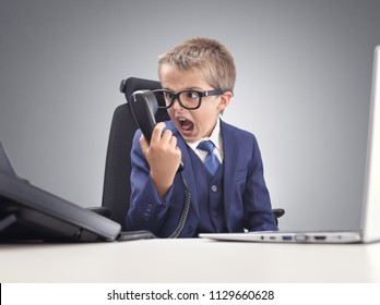 Angry young child businessman shouting into a telephone