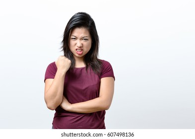 Angry young Chinese woman standing snarling at the camera and shaking her fist with a baleful glare over white with copy space