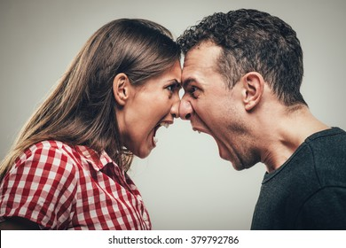 Angry young couple shouting face to face.