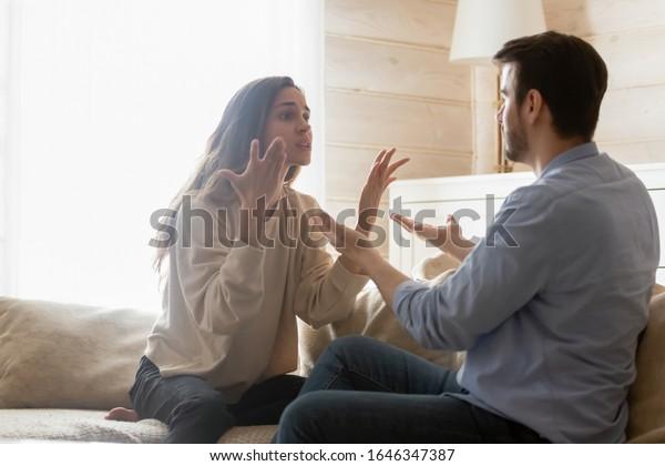 怒った若い夫婦は居間の長椅子に座り、家族の争いをしたり、勘違いをしたり、夫婦げんかをしたり、議論に巻き込まれた数千年の夫婦の争い、人間関係の問題のコンセプトに悩む