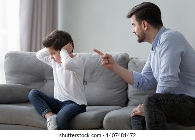 Angry young dad sit on couch lecture scold preschooler son closing ears with hands, offended stubborn boy child avoid ignore listening to serious mad father talking, having dispute or quarrel at home