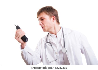 Angry young doctor with phone against white background.