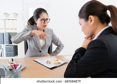 angry young female business manager pointing blame her employee sales woman when she finding company marketing very bad.