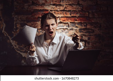 Angry young female entrepreneur with documents in hand looking at camera and shouting while sitting at table with laptop against brick wall