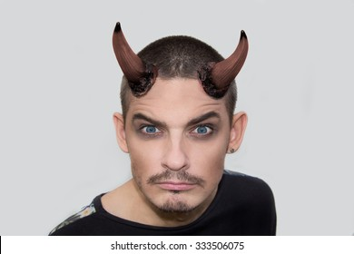 Angry young man with halloween horns on white background
