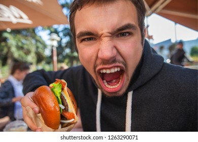 Angry young man looking at the camera with his mouth wide open. He is holding his hamburger at his right hand. Bad taste concept.