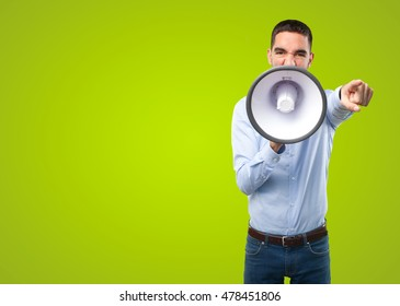 Angry young man with a megaphone on green background