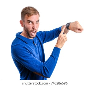 Angry young man pointing at his watch isolated on white background