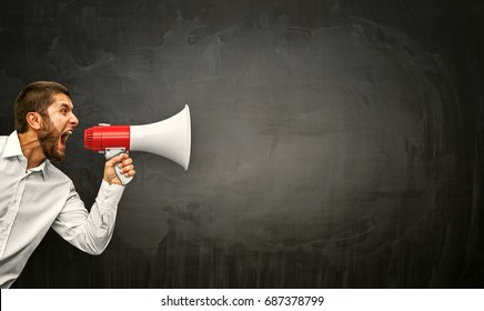 Angry young man shouting megaphone on grunge background