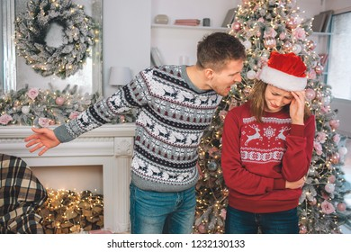 Angry young man stands close to woman and screams at her. He points left. Model is upset. She cries. They wear Christmas clothes.