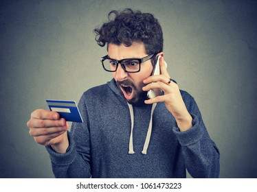 Angry young man talking on the phone while holding credit card and arguing expressively.