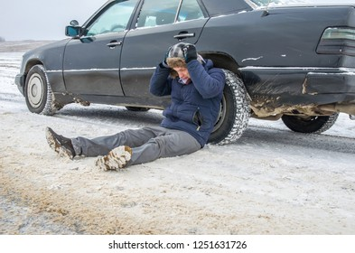 Angry young man waiting for help, sitting near a broken car on the side of the road in the winter in the forest and grabbed his head
