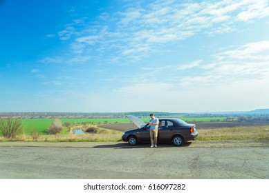 Angry young man waiting a help while sitting near the broken car at the side of road